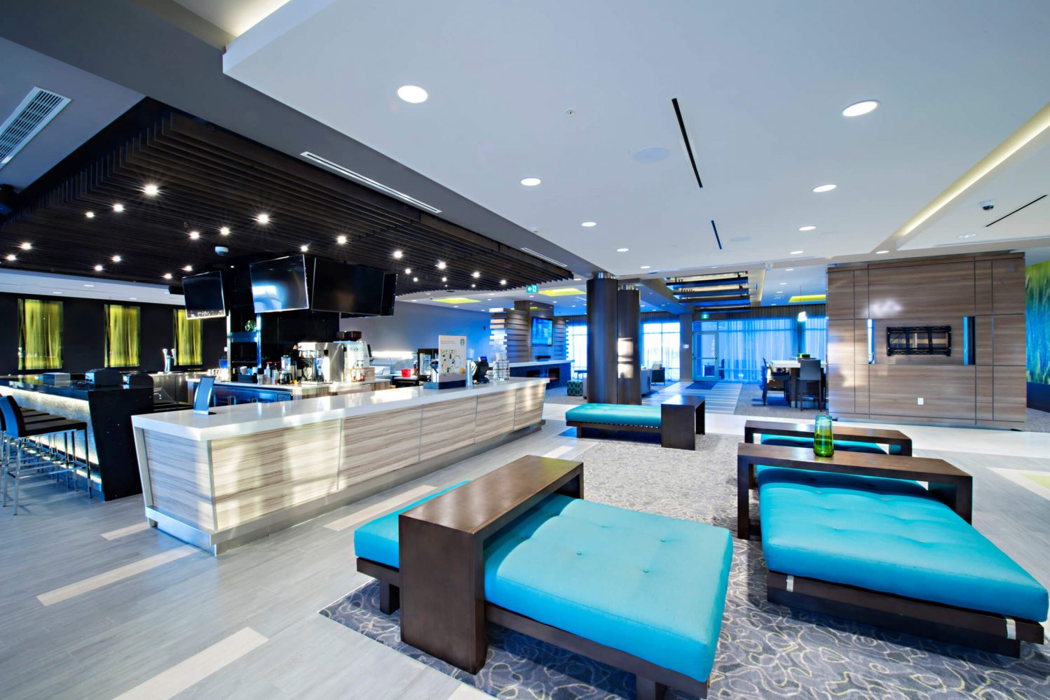 bar with blue cushioned chairs, tables, lights, and alcoholic drinks