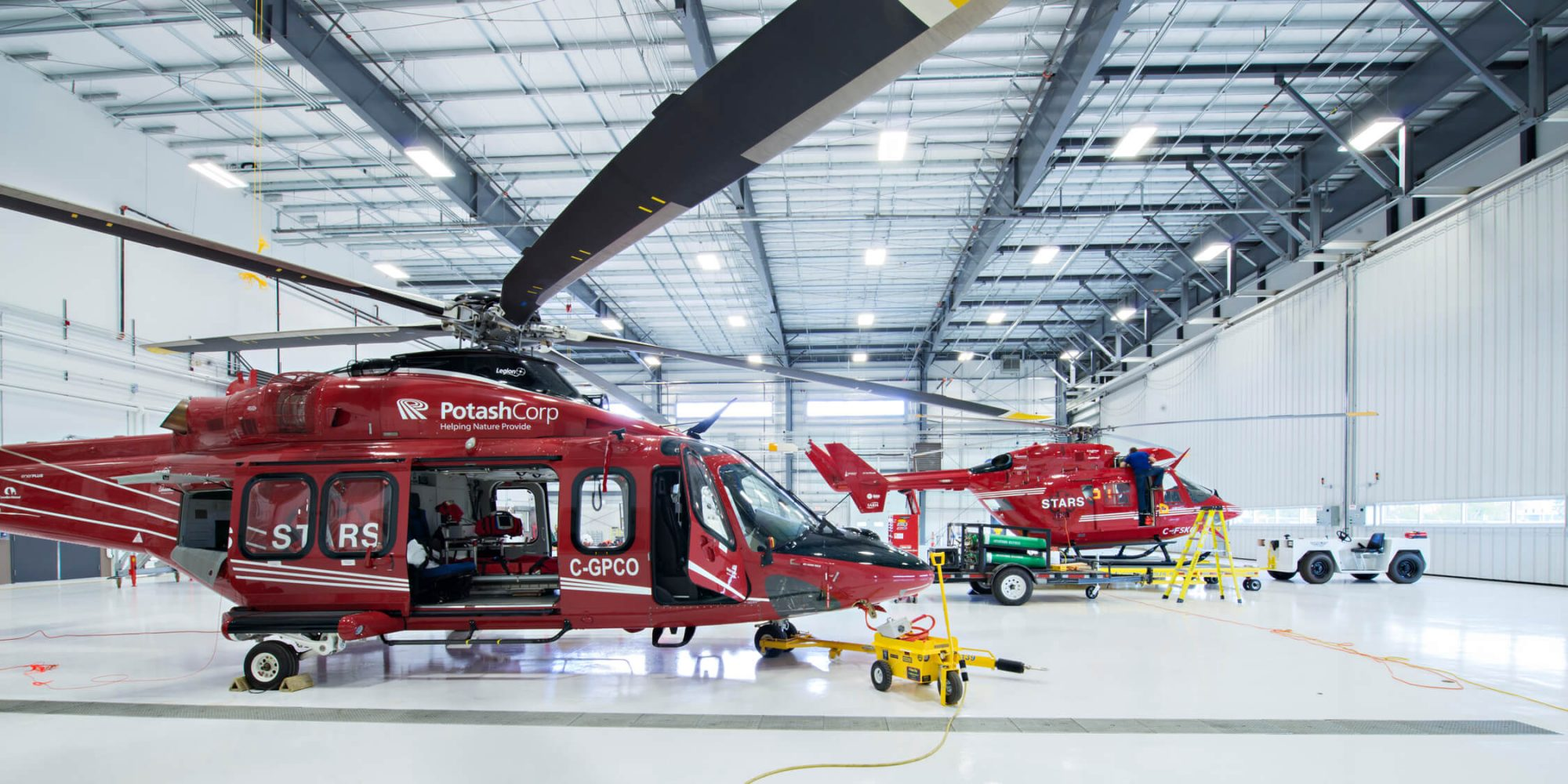 two red painted helicopters stationed in white warehouse