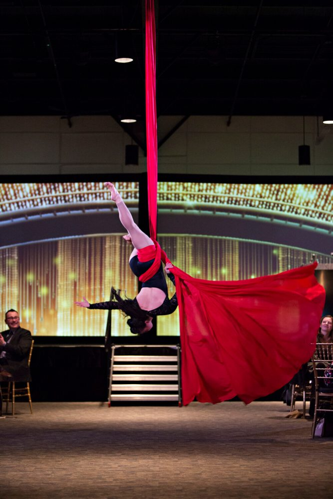 stunt-woman performing at a show using a big red ribbon