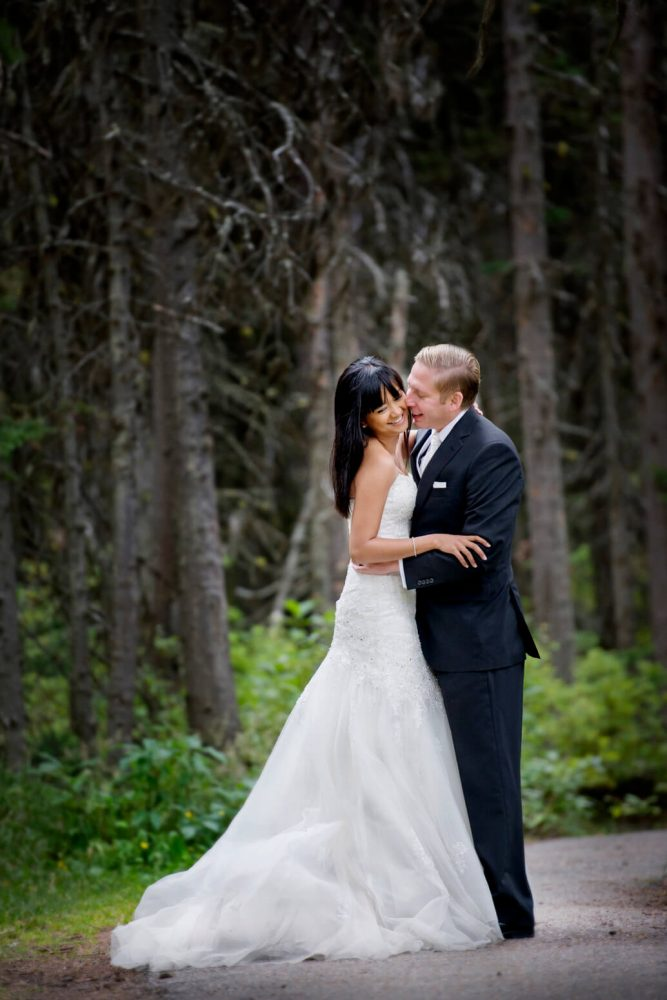bride and groom holding each other and posing in woods