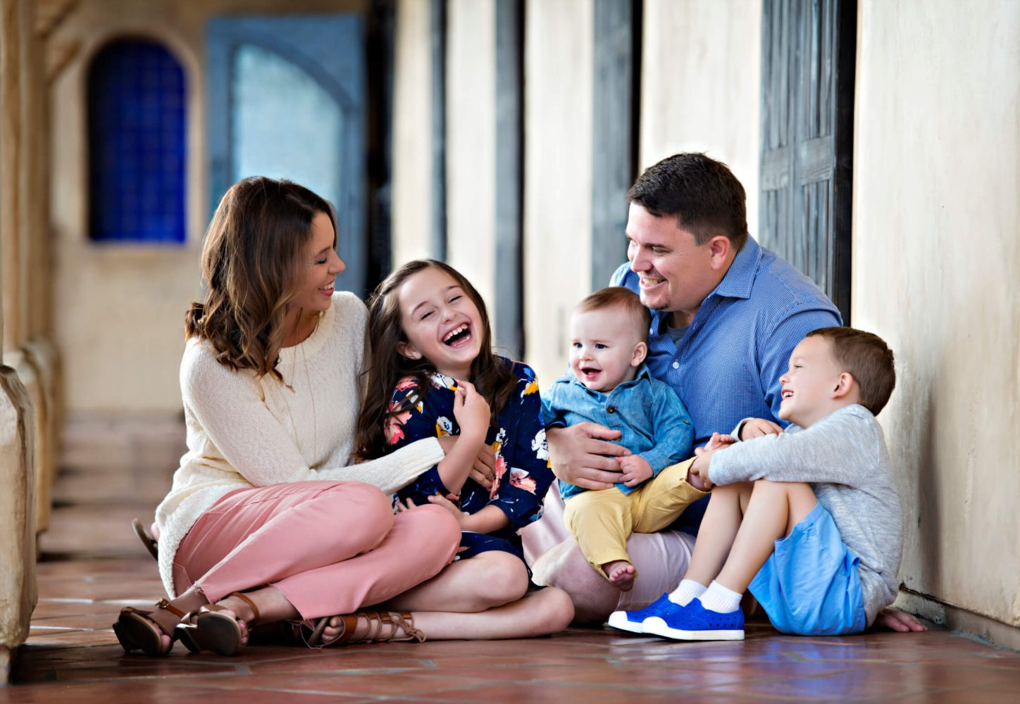 family laughing and posing inside building