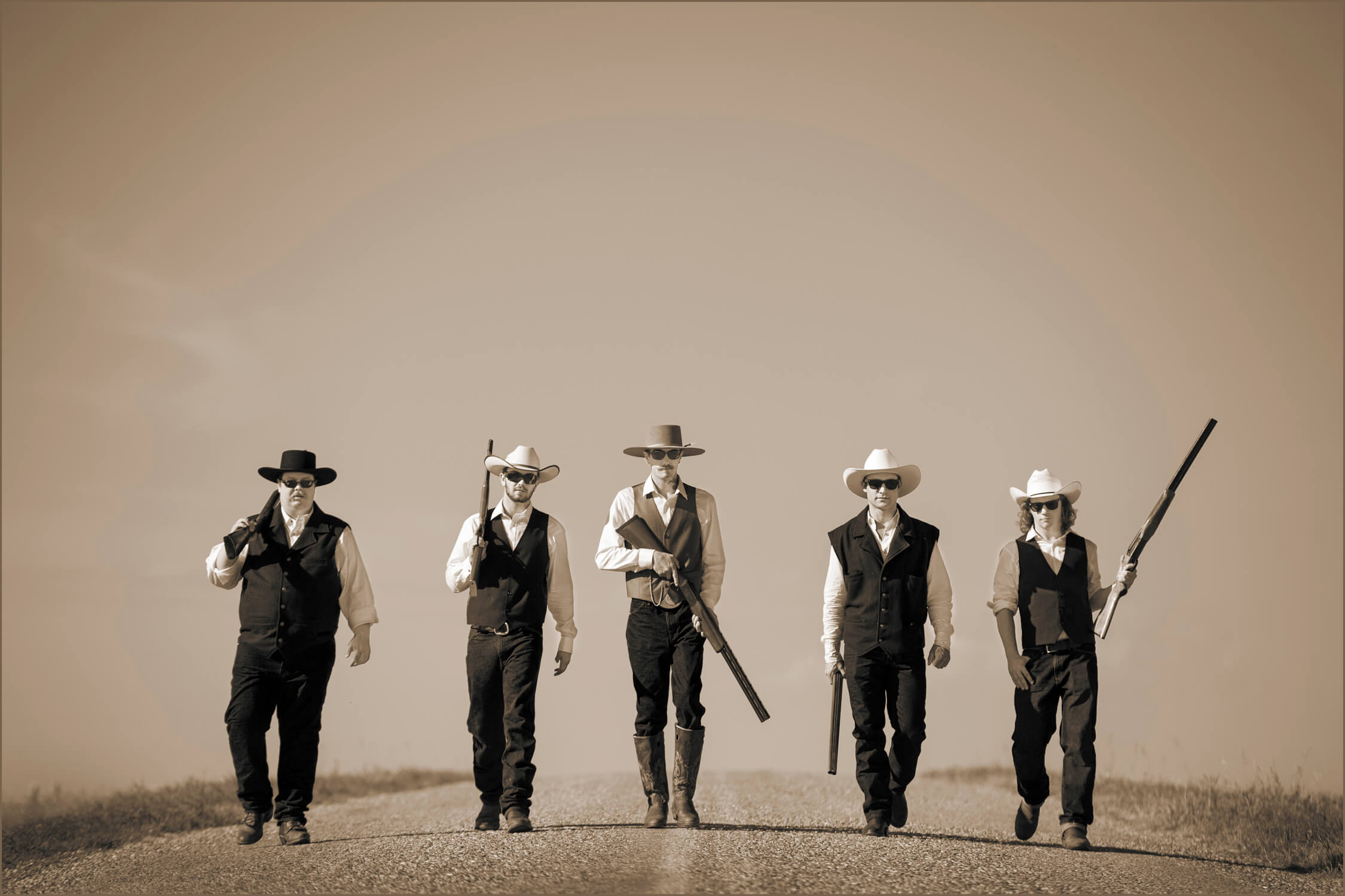 groom and groomsmen walking on open road holding guns