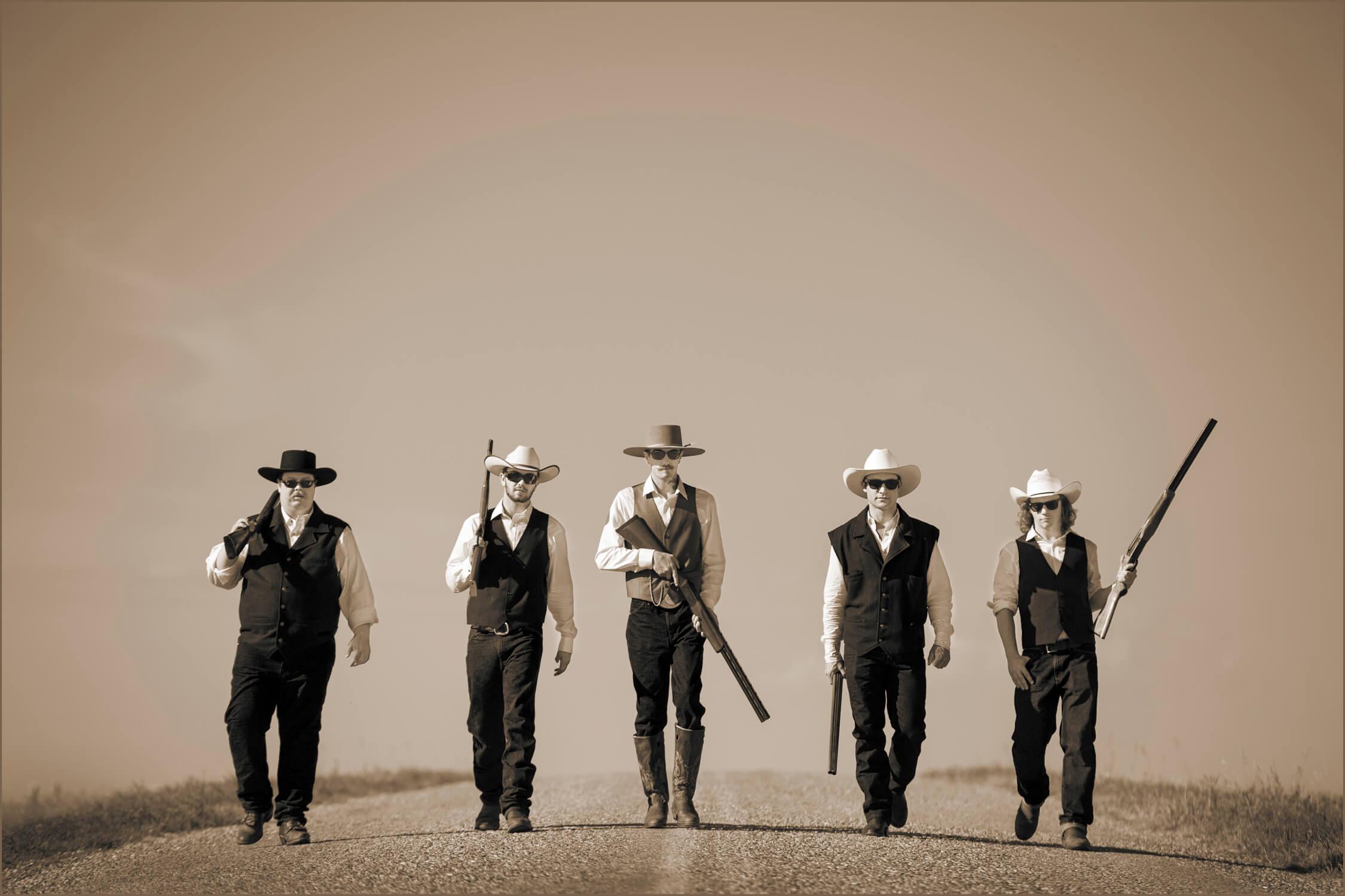groom and groomsmen walking on open road holding guns